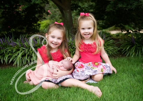 newborn girl outside with sisters