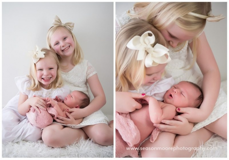 big sister on white with newborn baby raleigh